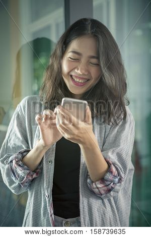 asian younger woman laughing with happiness emotion looking and reading chat message on smart phone