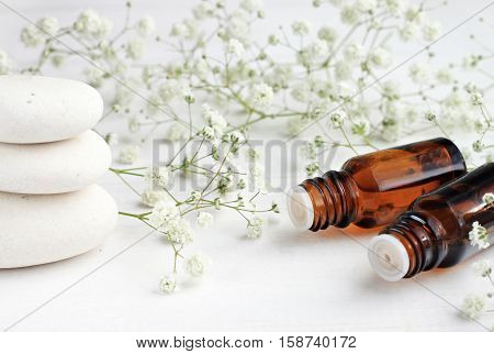 Tranquil white aromatherapy setting. Dropper bottles of aroma herbal essence, green and white airy flower decor, spa stones.