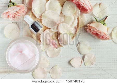 Plant-based aromatic cosmetic products. Pink facial mask, dropper with essential oil, rose flower petals, top view, pastel tender colors.