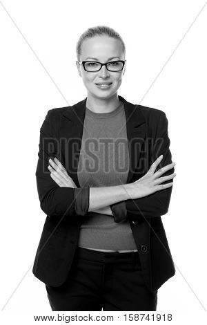 Black and white portrait of beautiful smart young businesswoman in business attire wearin black eyeglasses, standing with arms crossed against white background.