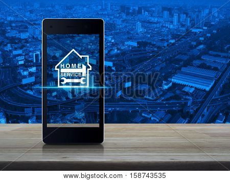 Hammer and wrench with house icon on modern smart phone screen on wooden table over city tower and expressway Home service concept