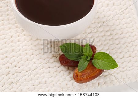 bowl of date syrup with dates on white table mat - close up