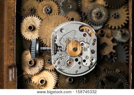 Aged mechanical clock macro view, rusty metal gears background. Shallow depth of field
