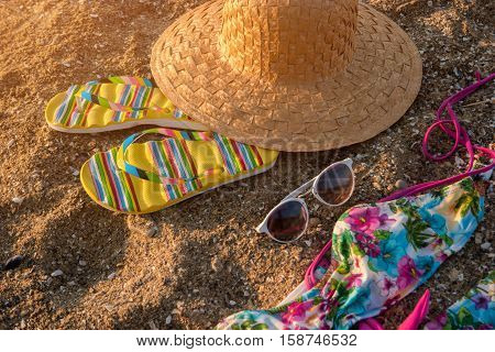 Beach hat and flip flops. Sunglasses lying on sand. Leave problems and bustle behind. Warm tropical resort.