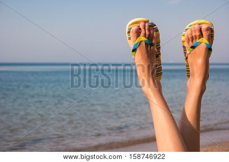 Woman's legs and sea. Feet wearing flip flops. Leave bustle and problems behind. The dream vacation.