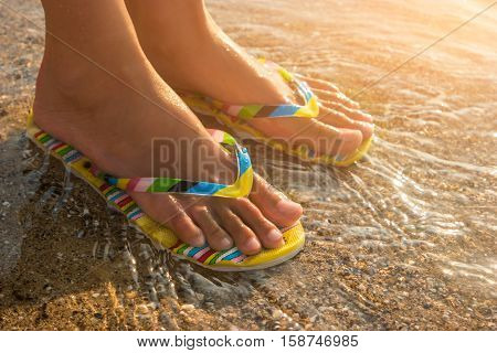 Female feet wearing flip flops. Water and sand under sunlight. One step away from sea. Visit a tropical island.