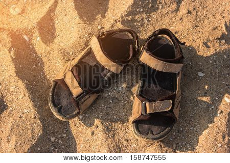 Sandals on sand. Footwear under sunlight. Hot tropical summer. Wander and explore.