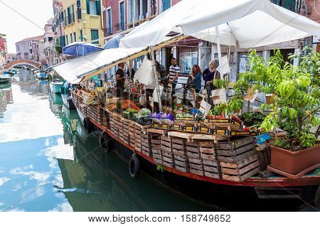 VENICE ITALY - MAY 27 2015: Floating market selling fruits and vegetables at Via Giuseppe Garibaldi in Venice Italy
