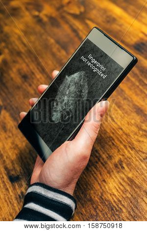 Fingerprint not recognized message on mobile smartphone screen after a sensor scan of female thumb failed to authenticate user and unlock electronics device