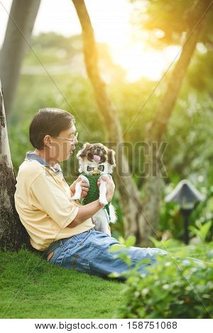 Singaporean man playing with his dog in the park