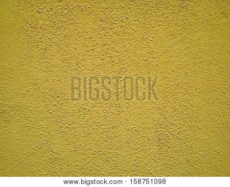 rough dark yellow plaster close up background