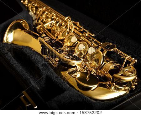 Saxophone detail against the background of a dark velvet cover.