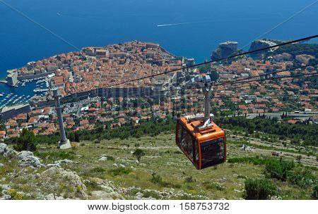 Dubrovnik Cable Car takes tourists from the old town to the top of Mount Srd. Old town city wall and the Adriatic sea in background.
