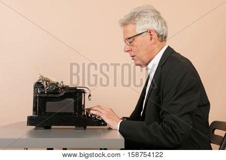 Senior man writing with Antique black typewriter