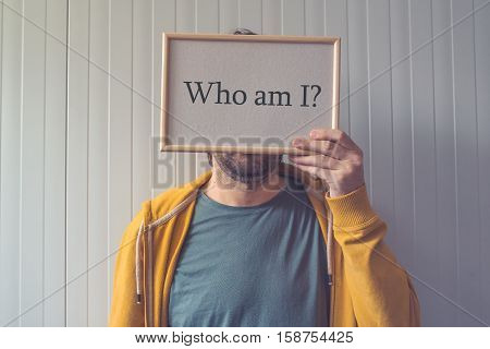 Who am I self-knowledge concept with question covering adult male face