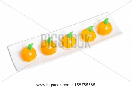 Delicious orange glazed cakes with mastic mint leaves. Isolated on a white background.