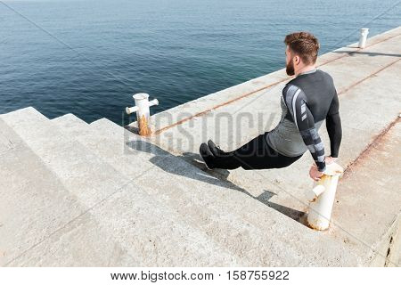 Workout exercise near the sea. man doing push ups. back view