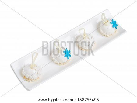 Delicious glazed cakes with coconut frosting and blue mastic snowflakes. Isolated on a white background.