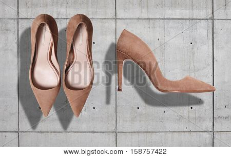Beige suede women's shoes with high heels shot from top and from the side isolated on neutral gray concrete background