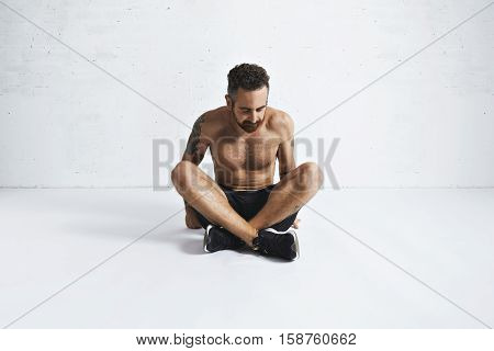 Calisthenics athlete takes a break after intensive workout, sitting on floor in gym, isolated on white
