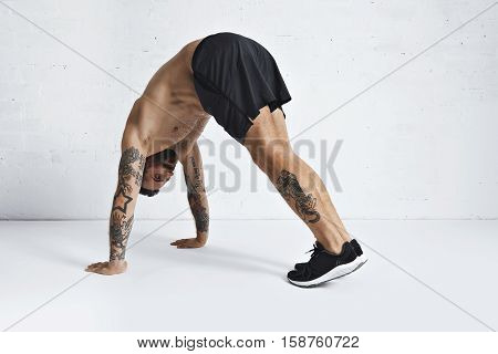 Strong brutal tattoed and ripped male athlete shows how to do pike push-ups, isolated on white spacious room, top position