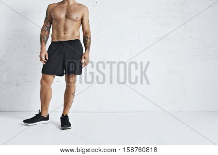 Tattooed unrecognizable sweaty calisthenics athlete takes a break after intensive workout, sitting on floor in gym, isolated on white