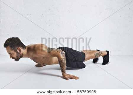Strong brutal tattoed and ripped male athlete shows how to do pseudo push-ups, isolated on white spacious room, low position