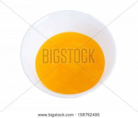 Mixed egg yolks in white bowl closeup. Isolated on a white background.