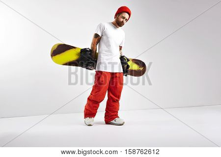 Rough muscular tattoed snowboarder in bright clothing and oversized blank white t-shirt walking with his snowboard behind his back isolated on white