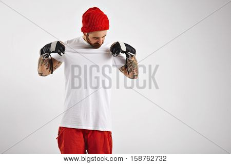 Young hipster boarder in red beanie and pants proudly presenting his clean blank white cotton t-shirt isolated on white