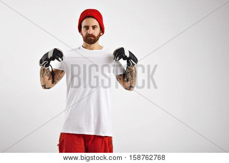 Young bearded and tattooed guy in snowboard pants and gloves and red beanie shows his unlabeled white t-shirt on white wall background