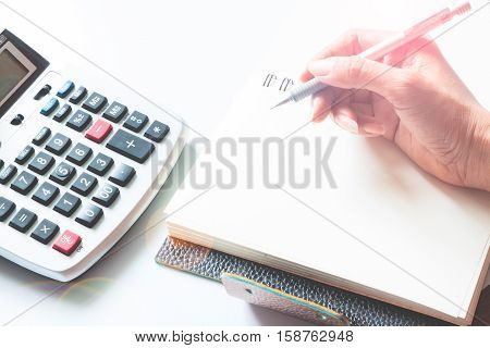 Accounting concept with calculator and hand holding pen on notebook