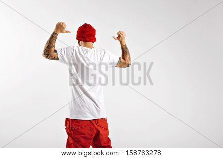 Athletic attractive snowboarder wearing red pants and beanie pointing at his plain white t-shirt shot from the back on white background