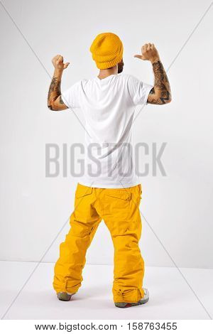 Young man in yellow snowboard pants and hat showing his unlabeled white cotton t-shirt shot from the back isolated on white