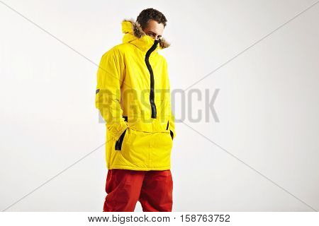 Fashionable attractive model in red skiing pants hiding his face into oversized bright yellow skiing anorak with hood isolated on white