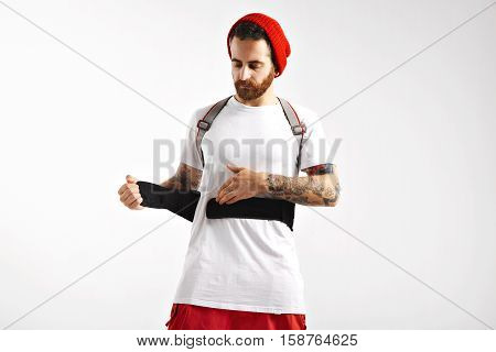 Focused serious snowboarder fastening the belly strap of his back protector over his white t-shirt isolated on white