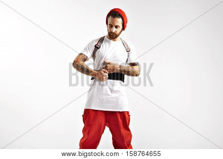 Serious focused snowboarder in red and white clothing tightening straps of his back protector in studio with white walls