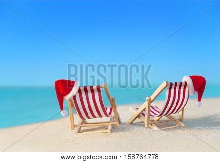 Two striped red-white sunloungers with Christmas Santa hats for romantic couple at ocean sandy beach New Year vacation in hot countries concept