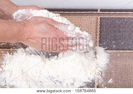 Male hands making dough with flour and grated butter on a table as a background.
