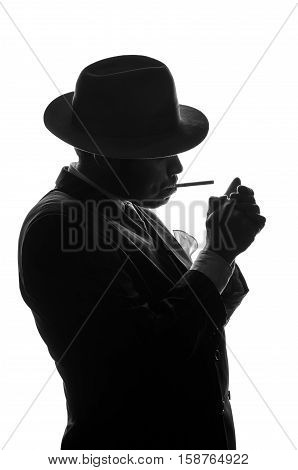 Silhouette of private detective in old fashion hat lights a cigarette. Gangster looks like mafiosi and stay side to camera. He wears a mob jacket. Police criminal scene in black and white. Studio shot isolated or cutout from background.