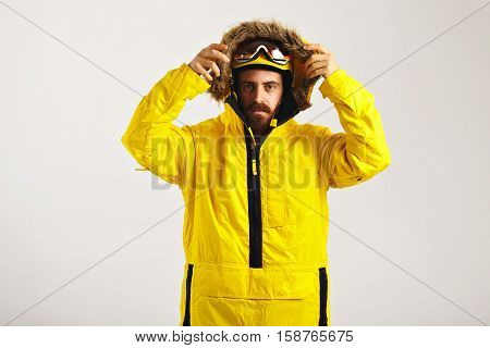 Serious young man in snowboard goggles and helmet putting up the hood of his bright yellow anorak coat isolated on white