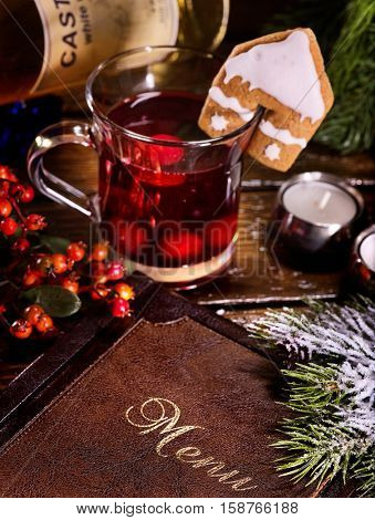 Part of menu book on cafe table. Ginger snap decorated tea mug. Spruce branch for decoration.
