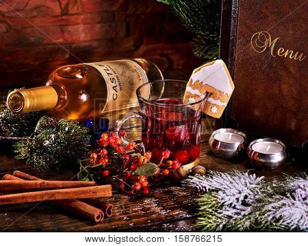 Menu card of warming cider cocktail with bottle of white wine . Label on bottle of wine. Bottle lying on snow-covered fir branches. Ginger snap in form of house decorated cider.