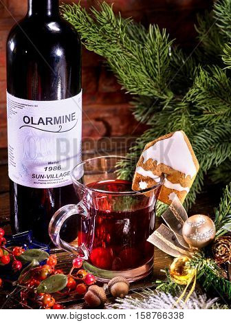 Bottle of red wine and mug with hot mulled wine. Label on bottle. Winter hot drink. Gingerbread cookie in form of house on mug.
