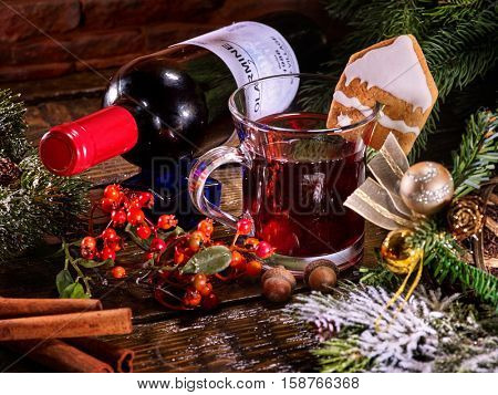 Red wine bottle with mug lying on snow-covered fir branches and winter berry Label on bottle. Gingerbread cookie in form of house on mug. Christmas ball and mulled wine.