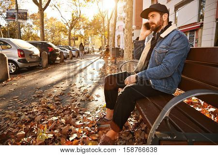 Attractive young man with a beard dressed in denim jacket, black trucker hat and black trousers sitting on a wooden bench in an autumn city street talking on the phone
