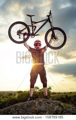 Professional Cyclist Riding the Bike Down Rocky Hill at Sunset. Extreme Sport Concept.
