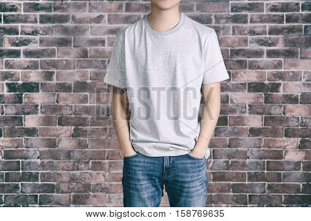 Young man in blank grey t-shirt standing against brick wall, close up