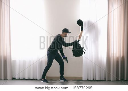 Male thieves with spoil near windows with curtains