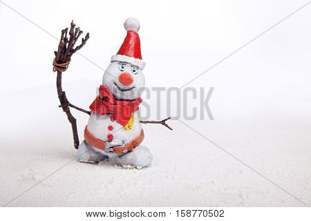 Christmas snowman in the snow with besom isolate on white